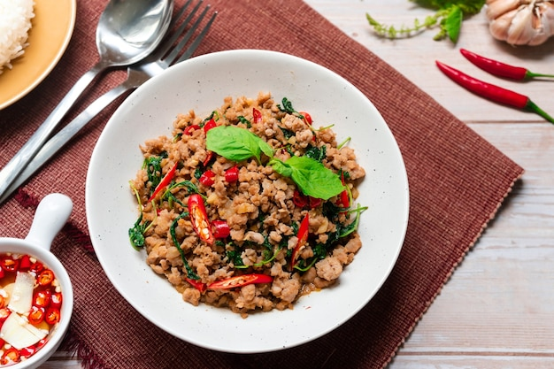 Top view of stirfried basil with minced pork on brown table cloth thai food dish
