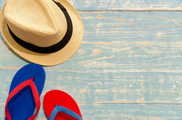 Top view of straw hat and flip flops on light blue wooden table. summer beach holiday concept with copy space.
