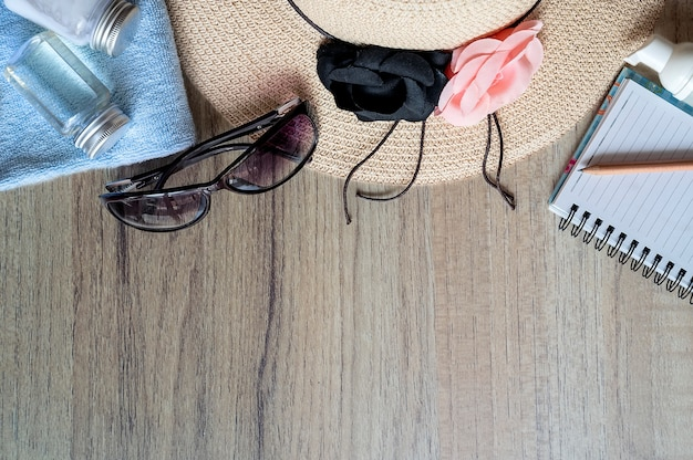 Top view straw hat, sunglasses, sunblock lotion and notebook on wooden table