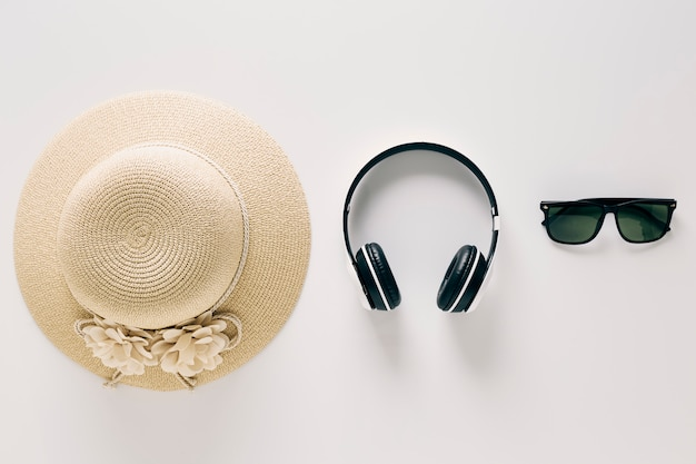 Top view straw hats with glasses and music headphones