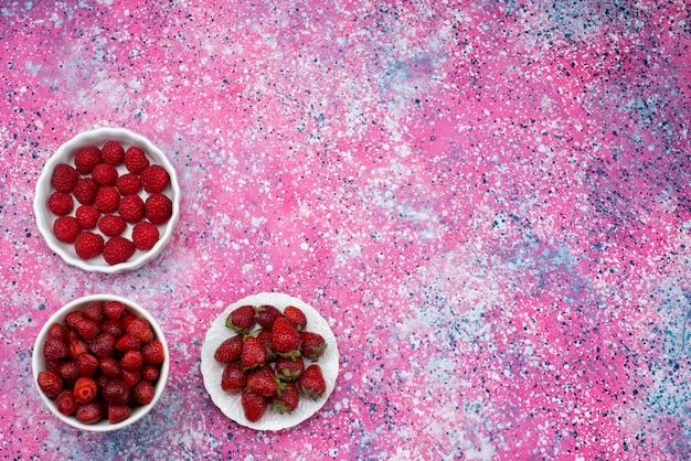 Вид сверху клубники и малины внутри белых тарелок на фиолетовом фоне, ягодный фруктовый цвет, свежий