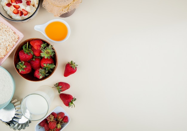 Top view of strawberries in bowl with cottage cheese butter milk oats on left side and white surface with copy space