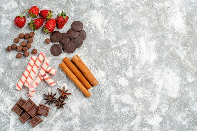 Top view strawberries chocolates candies cereals cinnamon anise seed at the left side of the grey-white table with free space