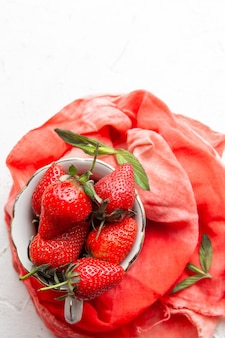 Top view strawberries in coffee cup on red cloth on white background. vertical