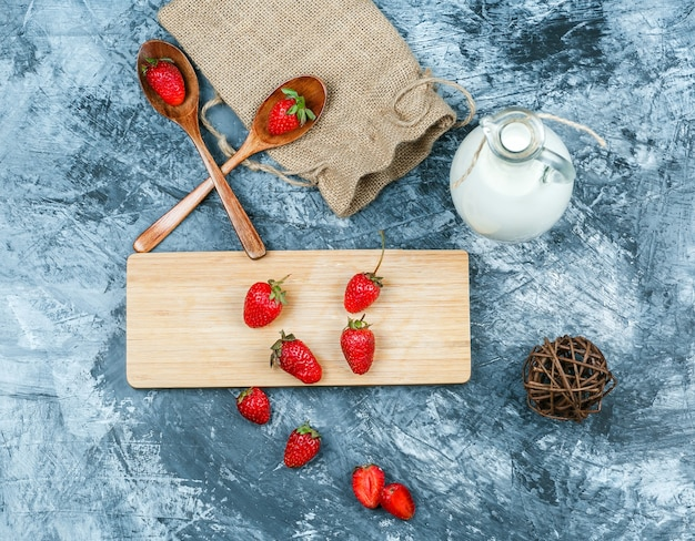 Top view strawberries on cutting board with milk,clew,wooden spoons and a piece of sack on dark blue marble surface. horizontal
