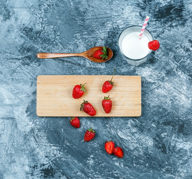 Top view strawberries on cutting board with milk and a wooden spoon on dark blue marble surface. horizontal