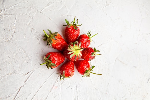Top view strawberries forming circle on white textured background. horizontal