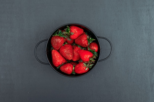 Top view strawberries in iron bowl on black background. horizontal