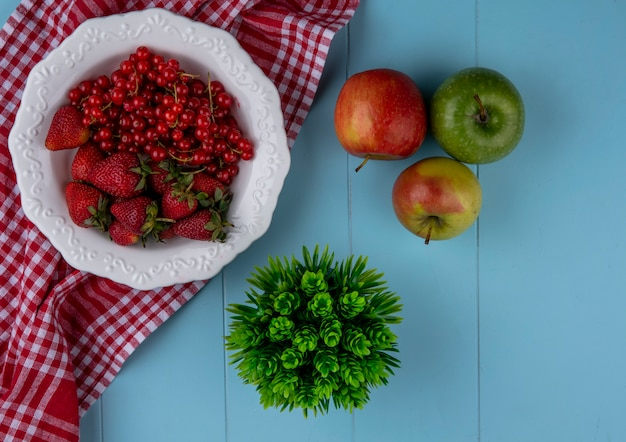 Top view strawberries with red currants on a plate with apples and a red kitchen towel on a light blue background