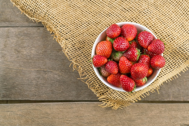 Top view of strawberry in bowl on wooden table.