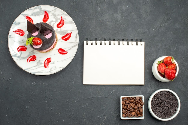 Top view strawberry cheesecake on oval plate bowls with strawberries chocolate coffee seeds a notepad on dark surface
