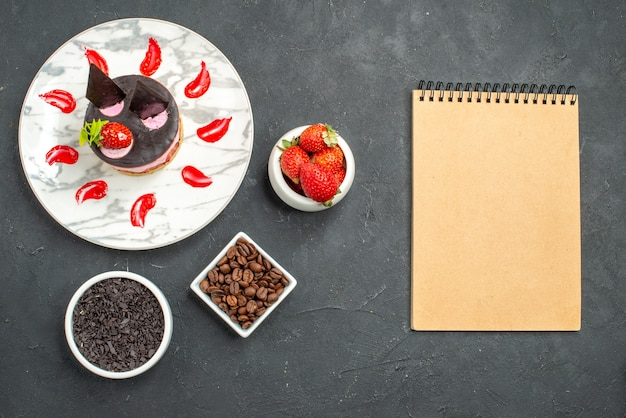 Top view strawberry cheesecake on white oval plate bowls with strawberries chocolate coffee bean seeds a notebook on dark surface