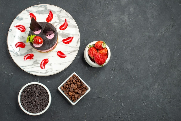 Top view strawberry cheesecake on white oval plate bowls with strawberries and chocolate coffee seeds on dark background