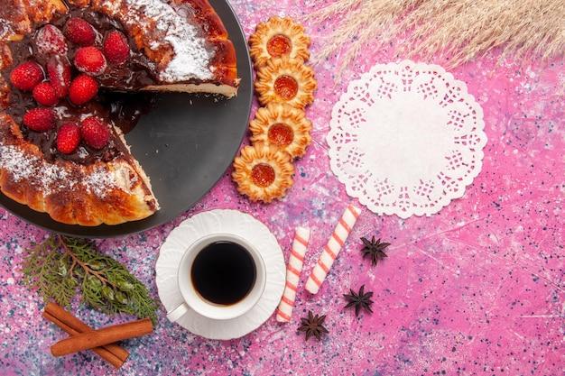 옅은 분홍색 표면에 있는 상위 뷰 딸기 초콜릿 케이크와 차 한 잔