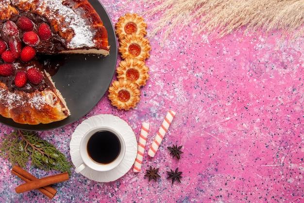 분홍색 표면에 있는 상위 뷰 딸기 초콜릿 케이크와 차 한 잔