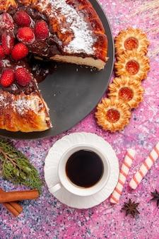 Torta al cioccolato alla fragola vista dall'alto con biscotti e tazza di tè sulla superficie rosa