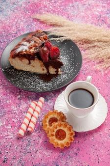 차 한 잔과 연한 분홍색 책상 위에 있는 꼭대기 전망 딸기 초콜릿 케이크