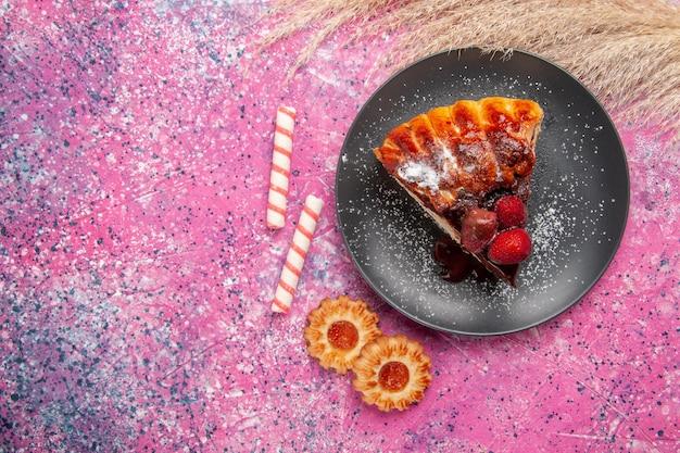 Вид сверху клубнично-шоколадный торт с маленьким на розовом столе