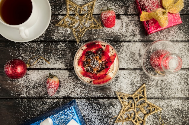 Top view of strawberry desert served with tea with christmas decorations