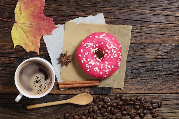 커피 한잔과 함께 접시에 상위 뷰 딸기 도넛