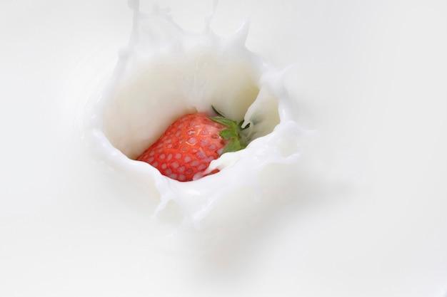 Вид сверху клубники, падающей в молоко
