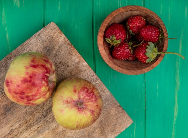 まな板の上にリンゴとボウルにイチゴの上面図