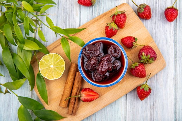 Top view of strawberry jam on a bowl on a wooden kitchen board with fresh strawberries with lime with leaves on a grey wooden background