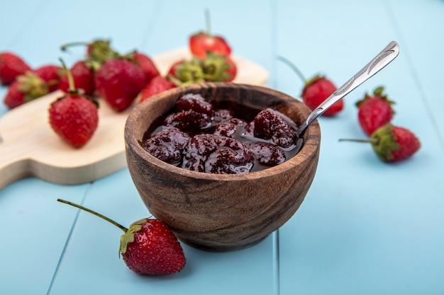 Vista dall'alto di marmellata di fragole su una ciotola di legno con un cucchiaino di fragole fresche su una tavola di cucina in legno su sfondo blu