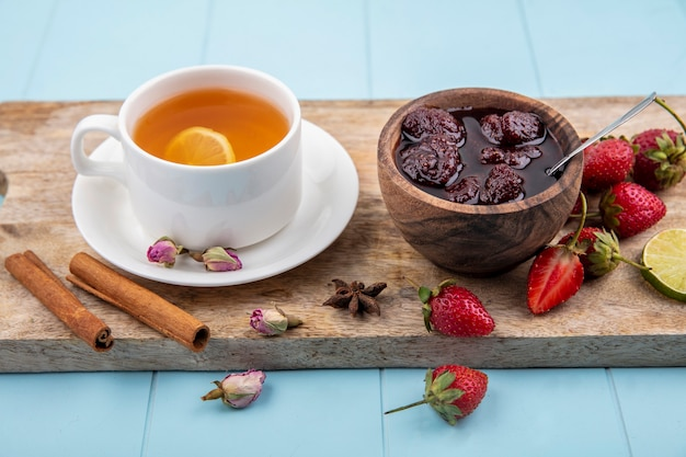 Top view of strawberry jam on a wooden bowl on a wooden kitchen board with a cup of tea with cinnamon on a blue background