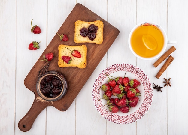 Top view of strawberry jam on a wooden kitchen board with toasted bread with fresh strawberries with cinnamon sticks on a white wooden background