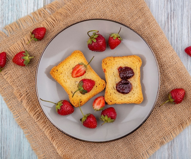 Top view of strawberry on toasted bread on a plate with fresh strawberries isolated on a sack cloth on a grey wooden background