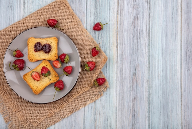 Top view of strawberry on toasted bread on a plate with fresh strawberries on a sack cloth on a grey wooden background with copy space
