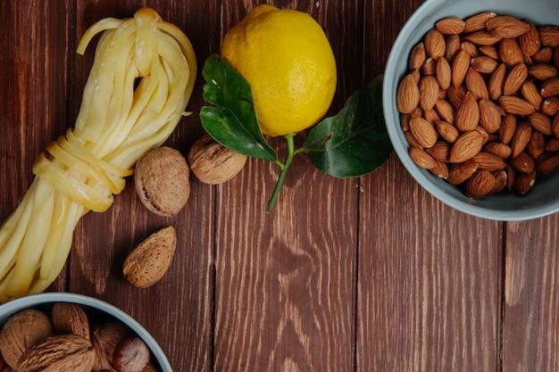 Vista dall'alto di formaggio a pasta filata con limone e mandorle in una ciotola blu su rustico