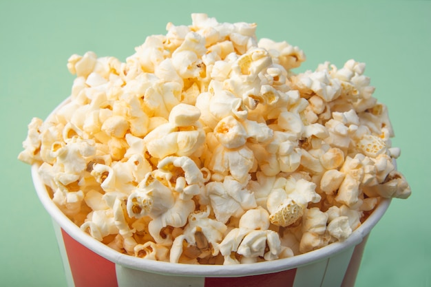 Top view of striped paper cup with popcorn. snack for a movie. close-up.