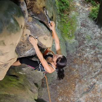 Top view of strong athletic woman climbing rock with rope