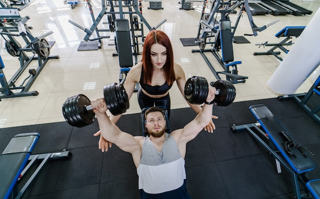 Top view of a strong man lifting dumbbells and a pretty woman helps him in gym. active couple exercising with dumbbells on a modern sports club.