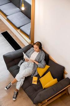 Studente con vista dall'alto che legge in biblioteca
