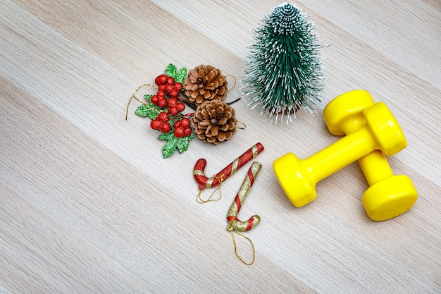 Top view studio shot of christmas eve and new year festival decorative items small mockup xmas tree pine seeds cherry fruit candy cane sticks and yellow dumbbells on wooden table with copy space.