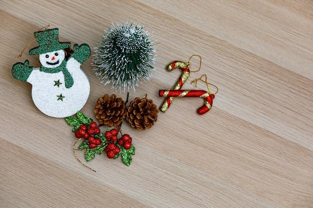 Вид сверху студийный снимок декоративных элементов фестиваля сочельник смайлик снеговик с зеленой шляпой, перчатки и шарф маленький макет дерева семена сосны плоды вишни и палочки леденцов на деревянном столе.