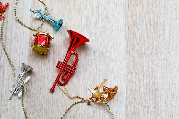 은색 밧줄에 장식용 음악 악기 기타 바이올린 드럼 트럼펫 트롬본을 매달고 복사 공간이 있는 밝은 갈색 나무 테이블에 금 사슬을 매달고 있는 작고 화려한 광택이 나는 스튜디오 샷.