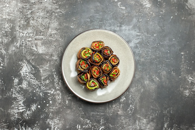 Top view stuffed aubergine rolls on grey background free space