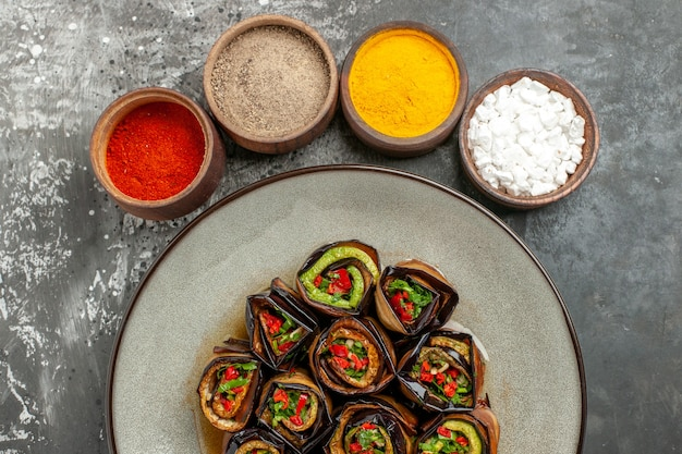 Top view stuffed aubergine rolls hot pepper powder turmeric in small bowls on grey background