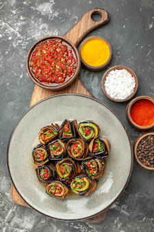 Top view stuffed aubergine rolls in oval plate adjika in bowl on wooden serving board different spices in small bawls on grey surface