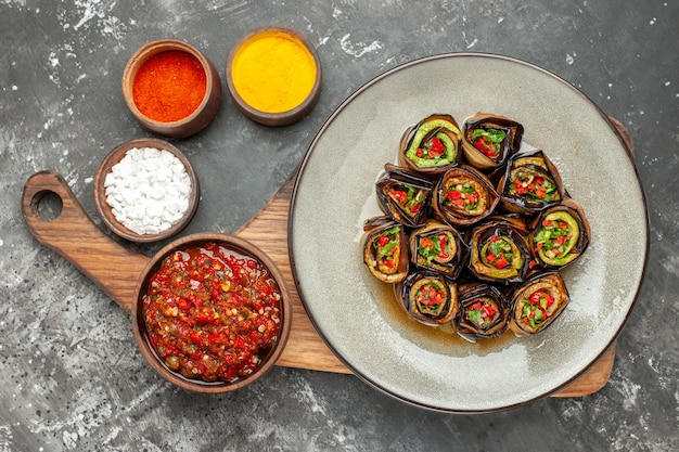 Top view stuffed aubergine rolls in oval plate adjika in bowl on wooden serving board with handle different spices in small bawls on grey surface