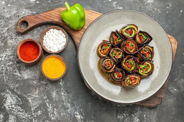 Vista dall'alto involtini di melanzane ripieni in piatto ovale un peperone verde su tavola da portata in legno con manico spezie diverse in piccole ciotole su sfondo grigio