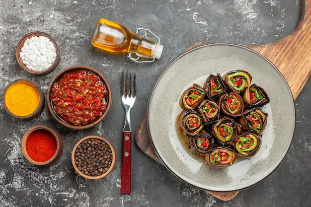 Top view stuffed aubergine rolls in oval plate on wooden serving board with handle different spices in small bawls adjika oil fork on grey surface