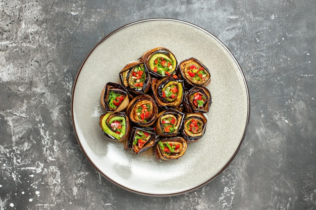 Top view stuffed aubergine rolls on plate on grey surface