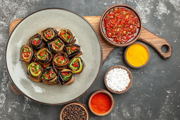 Top view stuffed aubergine rolls in white oval plate adjika in bowl on wooden serving board with handle different spices in small bawls on grey surface
