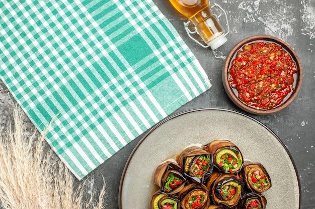 Vista dall'alto involtini di melanzane ripieni in piatto ovale bianco adjika in una piccola ciotola olio per tovaglia turchese-bianco su superficie grigia