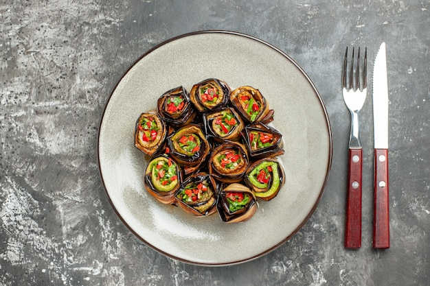 Top view stuffed aubergine rolls on white oval plate fork and knife on grey surface